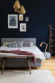Gilt lamp on blue bedroom wall