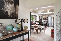 View past collection of globes into open-plan kitchen with dining area