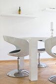 Glossy shell chairs and chunky table in white modern dining room