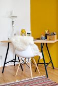 Desk with wooden top on metal frame and sheepskin on shell chair in corner against yellow wall