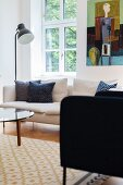 Armchair and standard lamp next to white sofa below lattice window and modern artwork