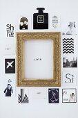 Postkarten und Fotos mit verschiedenen Motiven um goldenen Bilderrahmen mit 'Love'-Botschaft an Wand