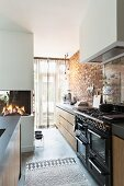 Vintage-style cooker and brick wall in modern kitchen