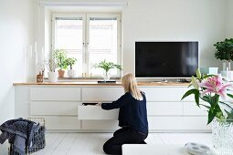 Woman in front of white fitted sideboard with drawers and flatscreen TV