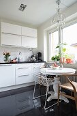 Round white table and various chairs in front of window and modern white kitchen counter