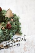 Wreath decorated with wooden Christmas trees next to candles wrapped in wire