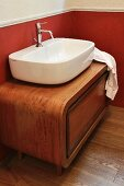 Countertop basin on rounded, exotic-wood base unit in renovated country-house bathroom with red wall below white dado rail