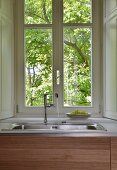 Water running from tap into sink below lattice window with view into garden