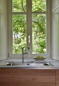 Spülbeckenarmatur mit Wasserstrahl vor Sprossenfenster mit Gartenblick