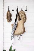 Vintage-Hakenleiste mit Strohhüten und Einkauftasche an weisser Holzverkleidung