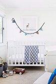 Helles Kinderzimmer mit weißem Gitterbett, Spielsachen und Wimpelkette als Wanddekoration