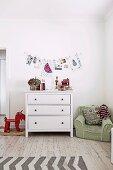 Kinderzimmer mit weisser Schubladenkommode, Schaukeltier und grünem Kindersessel, Wanddekoration mit Zeichnungen und Fotos an Wäscheleine
