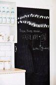 Schwarze, beschriftete Tafeltür neben weisser Küchenzeile