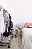 Damenkleidung auf fahrbarem Kleiderständer neben Bett im Schlafzimmer