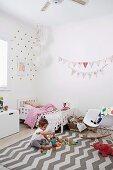Helles Mädchenzimmer mit Stoffwimpelkette und spielendem Mädchen auf Teppich