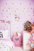 Mädchen im rosafarbenen Kinderzimmer mit gepunkteter Wand