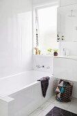 Weißes Badezimmer mit Wanne unter dem Fenster