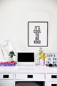 Schwarz gerahmter Spruch über einem Schreibtisches mit Laptop