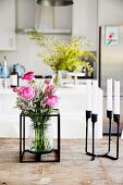 Blumenstrauss in Glasvase mit Metallgestell und Kerzenhalter aus schwarzem Metall