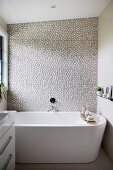 Freestanding bathtub in front of wall with pebble wall