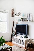Corner of living room with hanging TV over sideboard with baskets