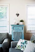 Gray upholstered furniture in front of windows with a half-height vintage cupboard and decorative heart