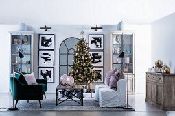 Christmas decorated living room with Christmas tree and symmetrical wall decoration with black framed pictures and display cabinets