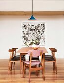 Wooden chairs with leather-covered upholstery around a table with retro flair in front of a wall with a modern image