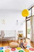 Child on carpet with colorful button pattern and cantilever armchair next to white cot