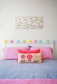 Girl's room with pink pillowcases, pastel colored fairy lights on white headboard and bird motif on wall