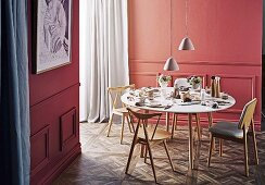 Round table with wooden chairs against salmon-colored wall