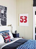 Bedroom with blue-white-red color accents, cushion cover with 'Union Jack' on bed