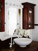 White washbowl on dark brown wooden base cabinet in front of wall mirror and narrow display cabinets