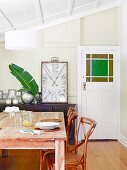 Wooden dining table and wooden chairs with wicker in front of a framed vintage clock on a sideboard in the attic