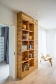 Open-fronted, floor-to-ceiling fitted bookcase in minimalist living area