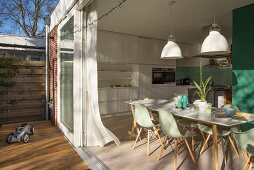 View from terrace into dining area with mint-green classic chairs and white fitted kitchen
