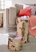 A stump of birch wood as a side table with the tops painted pink