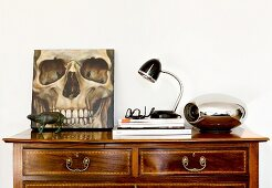 Picture of skull on top of antique chest of drawers