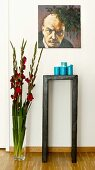 Portrait of Lenin above candles on console table and floor vase of gladioli