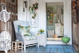 Wicker armchair on cosy terrace with board walls