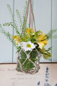 Glass vase of flowers in macrame hanger