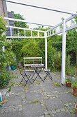 Gartenstühle und Tisch auf Terrasse mit weiss lackiertem Pergolagestell und Betonplatten