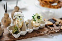 Eierkarton mit vergoldeten Eiern als Blumenväschen, Federschmuck und Holzhäschen