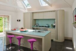 Island counter with bar stools and fitted counter with sliding door in modern kitchen