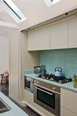 Fitted appliances in modern kitchen counter with sliding door