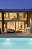 Pool and outdoor furniture on terrace outside contemporary house with illuminated interior