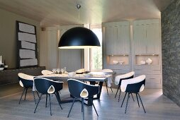 Pendant lamp with black hemispherical lampshade above dining set with designer chairs