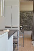 Minimalist dining area in front of partition cabinets next to doorway with view of stone wall