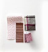Pinned fabric and wallpaper swatches in purple tones