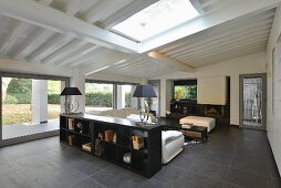 Modern, black and white living room with glass wall under sloping ceiling